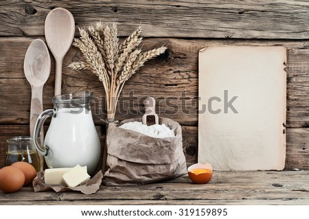 Baking ingredients eggs, flour, milk, butter, sunflower oil on wooden background with a blank sheet. Top view. Free space for text. Food background - stock photo