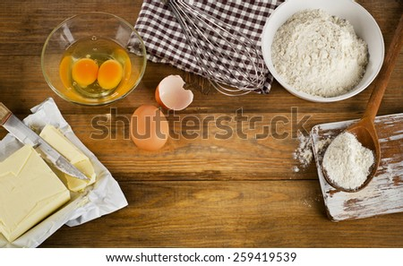 baking ingredients eggs, flour, sugar, butter on old wooden background