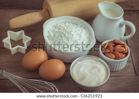 Baking ingredients flour, egg, milk, almonds, sugar on wooden table, Filtered image