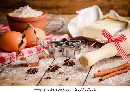 Baking ingredients - flour, eggs, butter and rolling pin, cookie cutters on a table