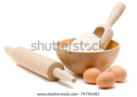 Baking ingredients - flour in bowl with eggs and rolling pin over white background