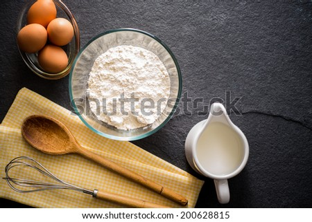 Baking ingredients - flour, milk, eggs with a whisk, wooden spoon and napkin on a slate background with copy space