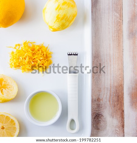 Baking ingredients for a lemon cake - whole lemon, lemon rind, squeezed lemon, lemon juice - stock photo