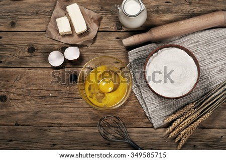 Baking ingredients (milk, eggs, flour, butter) in the bakery on a rustic table. Top view with copy space - stock photo
