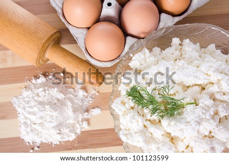 Baking ingredients, milk, flour, eggs and cheese on the table - stock photo