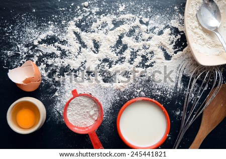 Baking ingredients on a dark, stone table: eggs, flour and milk. A lot of copyspace.