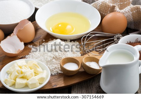Baking ingredients on a wooden board, horizontal, close-up - stock photo
