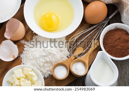 Baking ingredients on a wooden board, top view, close-up - stock photo