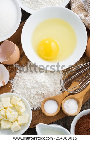 Baking ingredients on a wooden board, vertical, top view, close-up - stock photo