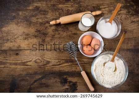baking ingredients on dark wooden table with empty space - stock photo