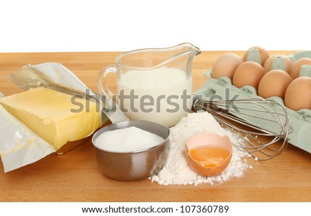 Baking ingredients, sugar,flour,eggs,milk and butter with a whisk on a wooden worktop - stock photo