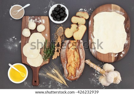 Baking ingredients with rustic bread loaf, dough, yeast, black olives, olive oil, garlic, herb and rye grain in a love spoon on maple wood over grey. - stock photo