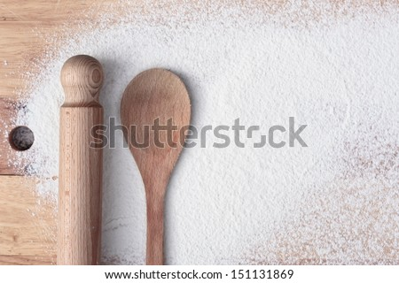Baking items and flour on a wooden surface - stock photo