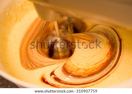 Baking of a Brownie - melted chocolate added into the mixture - stock photo
