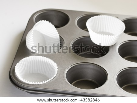 Baking pan and paper cups for muffins - stock photo