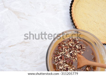 Baking pecan pie - nut-filled pie filling in a bowl next to the prepared pie crust, with copy space on the kitchen worktop - stock photo