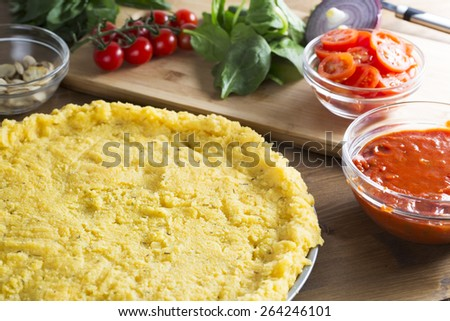 Baking polenta pizza, polenta pizza crust ready for toppings with bowl of tomato sauce to the side and tomatoes, spinach and mushrooms next to pizza crust. - stock photo