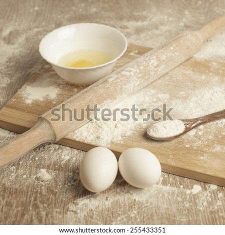 Baking. Preparations for homemade baking. Basic ingredients for baking. Kitchen utensil with eggs rolling-pin wood spoon meal. Meal on table with cutting board. Flour - stock photo