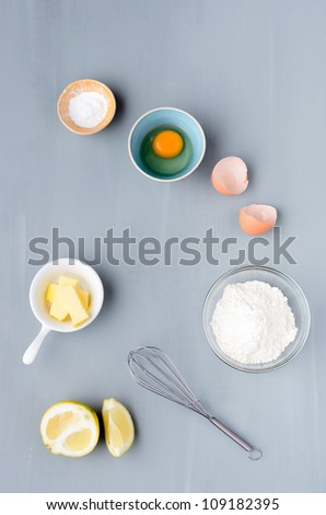 Baking raw ingredients flour, eggs, sugar shot from overhead on a grey background - stock photo