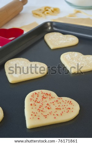 Baking sheet of heart shaped cookies with white and red sprinkles