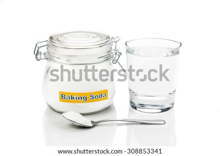 Baking soda in jar, spoonful and glass of water for multiple holistic usages. - stock photo