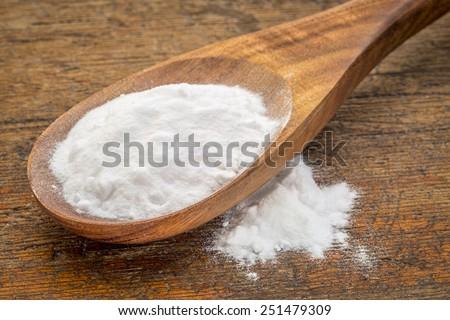 baking soda (Sodium bicarbonate) on a wooden spoon - stock photo