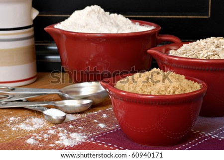 Baking still life of ceramic measuring cups and stainless steel spoons filled with ingredients.  Flour dusted in foreground.  Macro with shallow dof. - stock photo