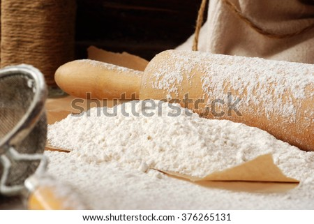 Baking still-life with flour heaped onto parchment paper, vintage wooden rolling pin, vintage sieve, and canvas flour sack with rope in background.  Closeup with shallow dof.  Selective focus on flour - stock photo