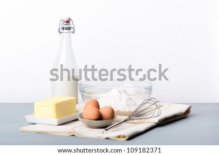 Baking still life with raw ingredients, flour, butter, eggs, milk to make dough, cakes, cookies - stock photo