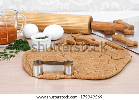 Baking supplies for making homemade healthy pumpkin dog biscuits.  Rolling pin, dough, pumpkin, parsley and eggs next to rolled out dog cookies.  Selective focus on dough. - stock photo