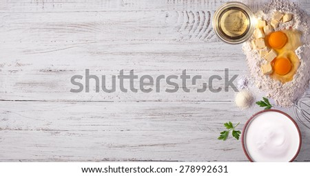 Baking tabletop background with eggs, olive oil, milk, flour, butter on white wooden background - stock photo