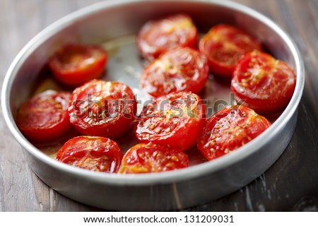 baking tray with cherry tomatoes drizzled with salt, olive oil and oregano - stock photo