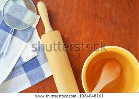 Baking utensils in flat lay on old wooden board with room for text