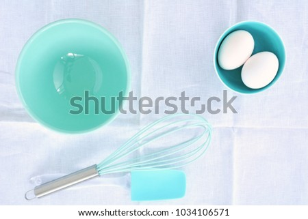 Baking utensils in turquoise theme on white linen in flat lay