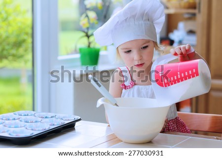Baking with children. Little happy kid, adorable toddler girl in white chef hat adding flour to the bowl with dough ingredients helping mother to prepare delicious pastry in the kitchen - stock photo