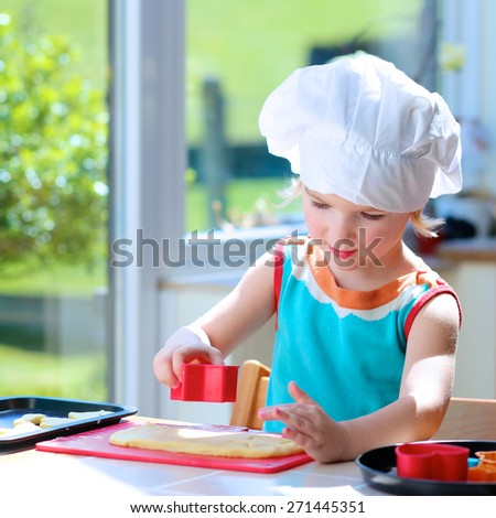 Baking with children: little happy kid, adorable toddler girl in white chef hat cutting the dough into animal shapes or other forms helping mother to prepare delicious pastry in the kitchen - stock photo