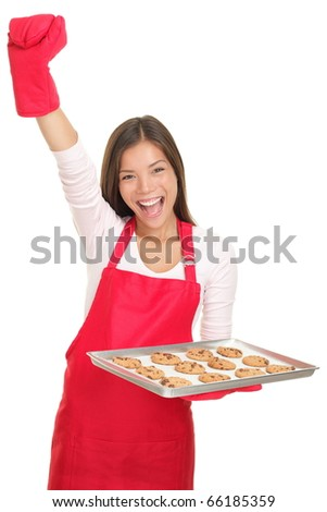 Baking woman excited with arm raised in success holding a tray of cookies. Young smiling Asian / Caucasian woman isolated on white background. - stock photo