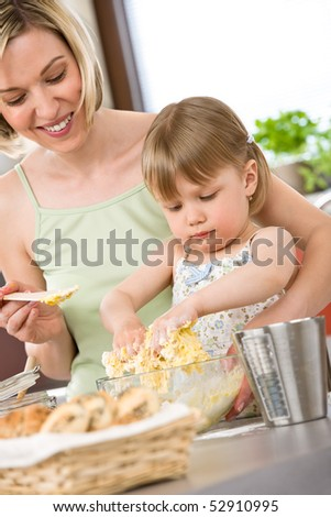 Baking - Woman with child preparing dough with healthy ingredients