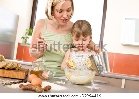 Baking - Woman with child preparing dough with healthy ingredients - stock photo