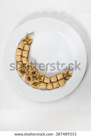 Baklava arranged in a shape of moon on white plate. Ramadan special food - stock image. - stock photo
