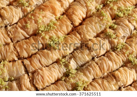 Baklava is a Middle-Eastern dessert. It is a rich, sweet pastry made of layers of filo filled with chopped nuts and sweetened and held together with honey. Suitable for an abstract background. - stock photo
