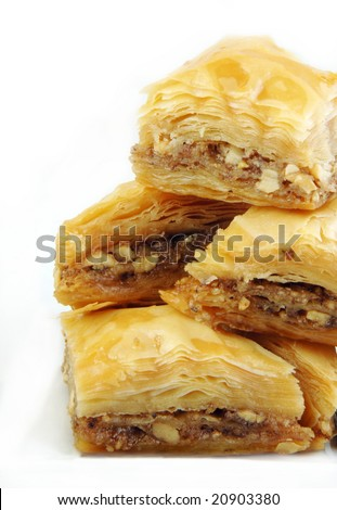 Baklava stacked up high on a white background. - stock photo