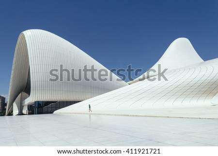 Baku, Azerbaijan-July 22, 2015: A woman walking past the Haydar Aliyev Centre designed by Zaha Hadid. The centre is well known for its distinctive, curvy architecture.