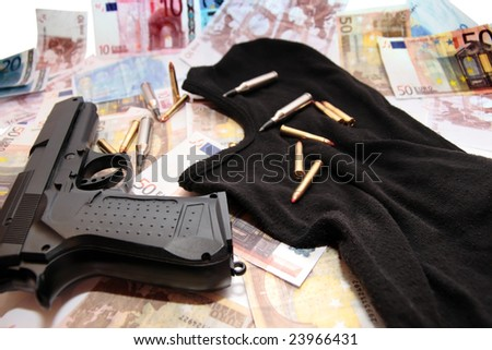 balaclava money gun and bullets showing a concept of a robbers or terrorists activity - stock photo