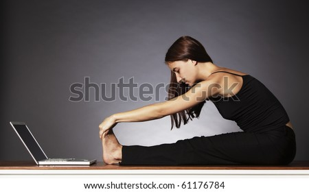Balance at work: Young pretty woman in black sitting in front of laptop and stretching her legs . - stock photo