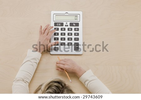 Balance at Zero - overhead shot of hands using calculator and top of woman's head in frame - stock photo