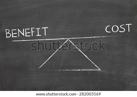 balance between benefit and cost written by hand on blackboard - stock photo
