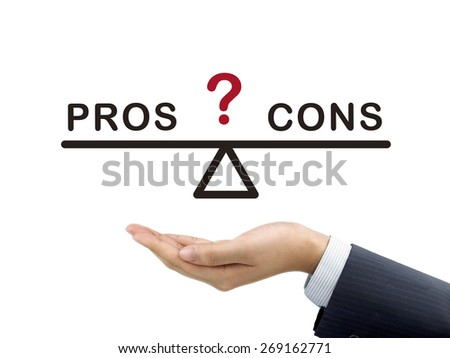 balance between pros and cons holding by businessman's hand over white background - stock photo