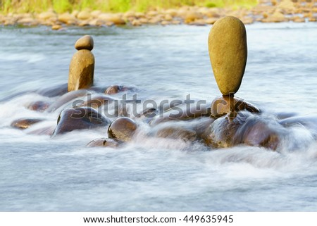 Balance stone in the middle of flowing river like zen garden.  - stock photo