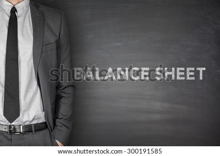 Balance text on black blackboard with businessman - stock photo